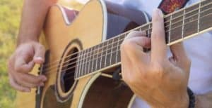 a man playing on an acoustic guitar that has a strap