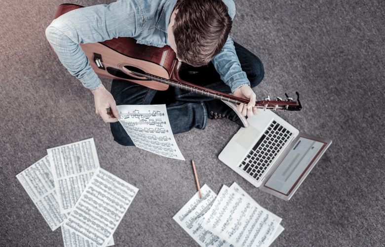 ambitious young man diligently learning guitar and reading tabs