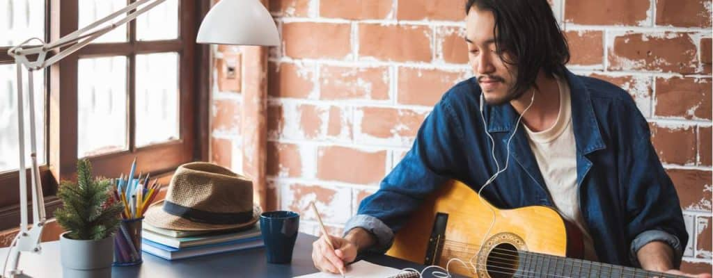 man writing on notepad for guitar songs